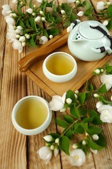 Chá de jasmim. chá de flor pura natural orgânico. chá de jasmim em xícaras redondas verdes claras, bule e ramos de jasmim