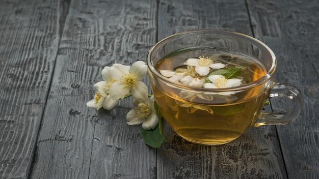 Chá de jasmim floral com flores em uma caneca de vidro sobre uma mesa de madeira.