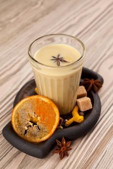 Chá de karak ou masala chai. bebida popular indiana em vidro na mesa de madeira.