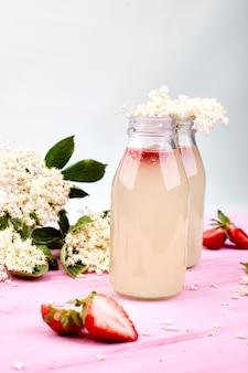 Chá de kombucha com sabugueiro e morango em fundo rosa.