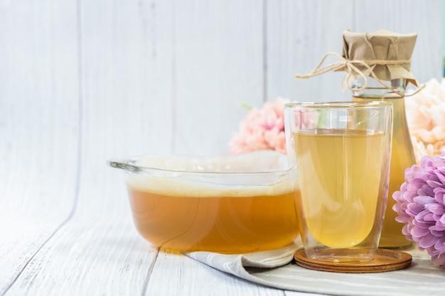 Chá de kombuchá em vidro com fundo de madeira, bebida fermentada de cidra.