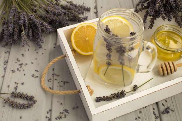 Chá de lavanda com mel e limão na bandeja de madeira branca