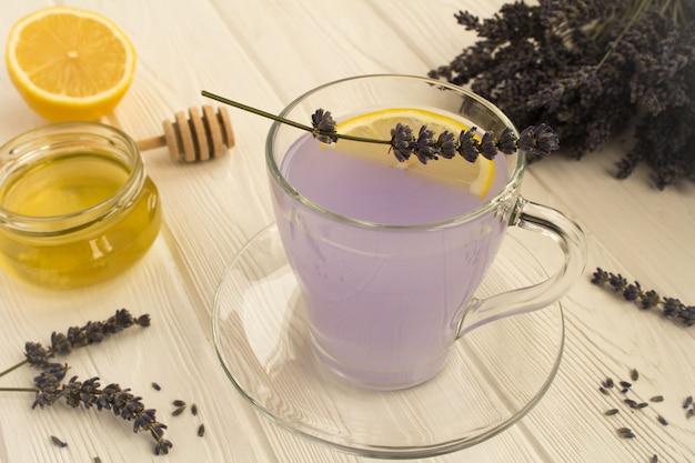 Chá de lavanda com mel e limão no fundo branco de madeira