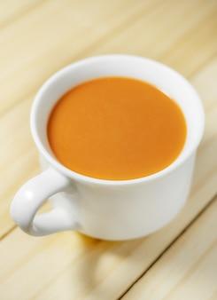Chá de leite quente em uma xícara branca em madeira