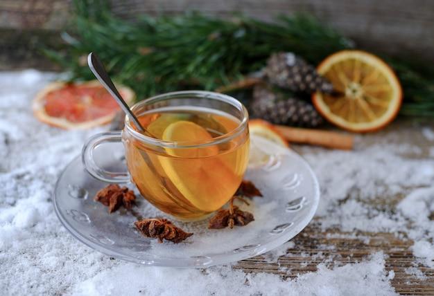 Chá de limão chinês vermelho em copo de vidro na mesa de madeira coberta de neve com galhos de pinheiro, cones, anis, laranjas secas