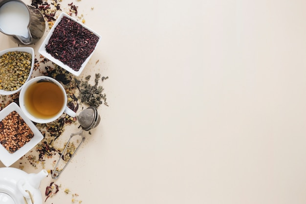 Chá de limão com folhas de chá secas; flores secas de crisântemo chinês; coador de chá; leite; ervas e bule em fundo colorido