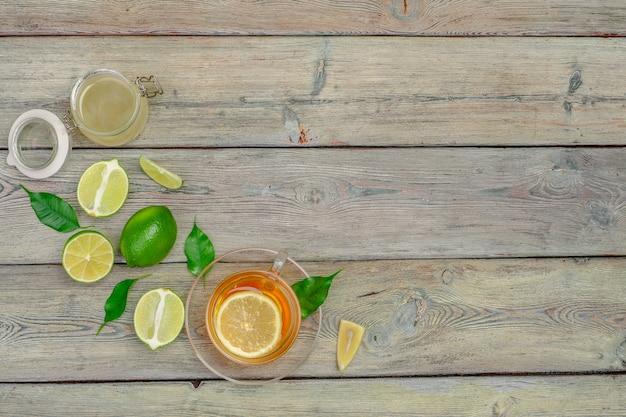 Chá de limão com limão e limão no fundo da mesa de madeira
