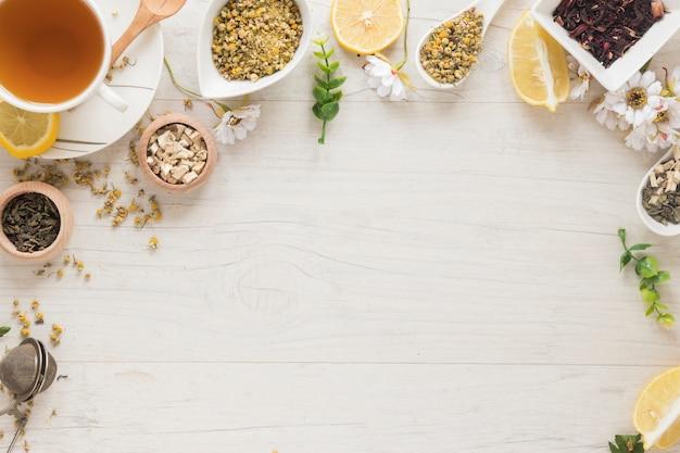 Chá de limão; flores secas de crisântemo chinês; ervas na mesa de madeira