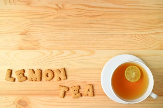 Chá de limão quente com a palavra chá de limão com biscoito de biscoitos na mesa de madeira