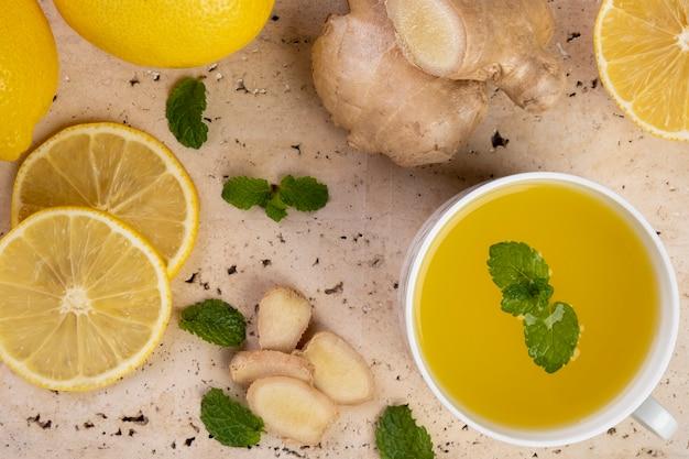 Chá de limão siciliano com gengibre e folhas de hortelã na pedra de mármore branca.