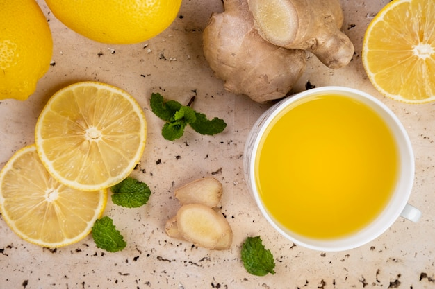 Chá de limão siciliano, gengibre e folhas de hortelã em pedra de mármore branca.