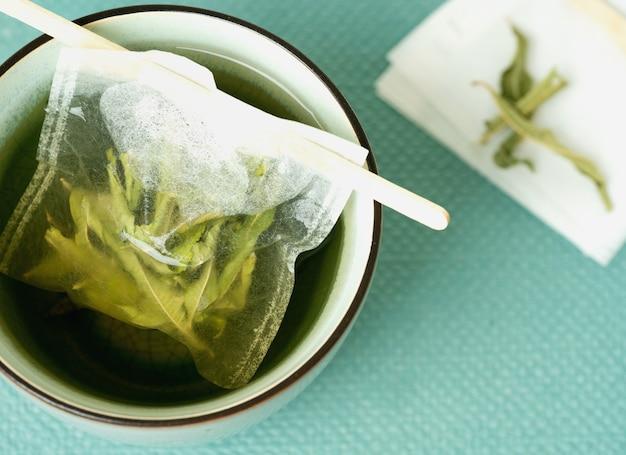 Chá de limão verbena em uma caneca com saquinho de chá feito à mão. vista do topo. lay flat.