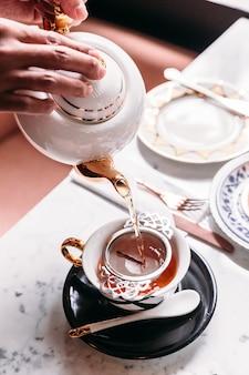 Chá de maçã quente servido derramando de caneca através de infusor de chá de aço inoxidável.