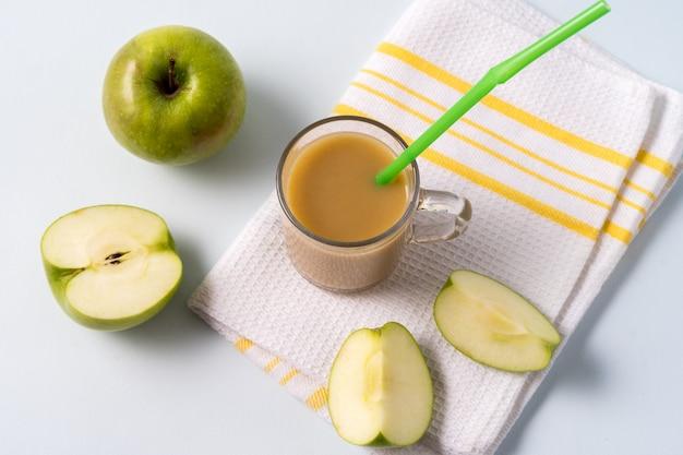 Chá de masala chai em um copo de vidro e maçãs frescas sobre o fundo branco.