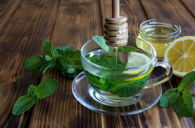 Chá de menta com mel no copo de vidro no fundo de madeira. fechar-se.
