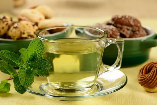 Chá de menta em copo transparente com biscoitos doces ao redor