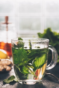 Chá de menta fresca perto da janela. casa ou saúde aconchegante