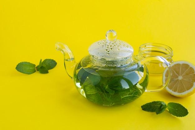 Chá de menta no bule de vidro, limão e mel no fundo amarelo. fechar-se. copie o espaço.