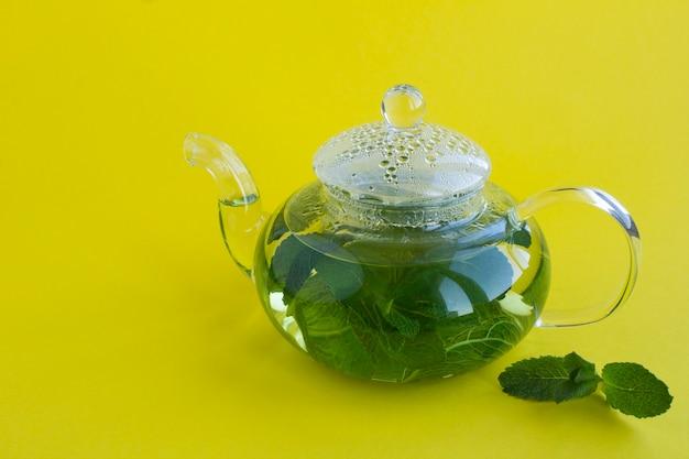 Chá de menta no bule de vidro na mesa amarela. fechar-se. copie o espaço.