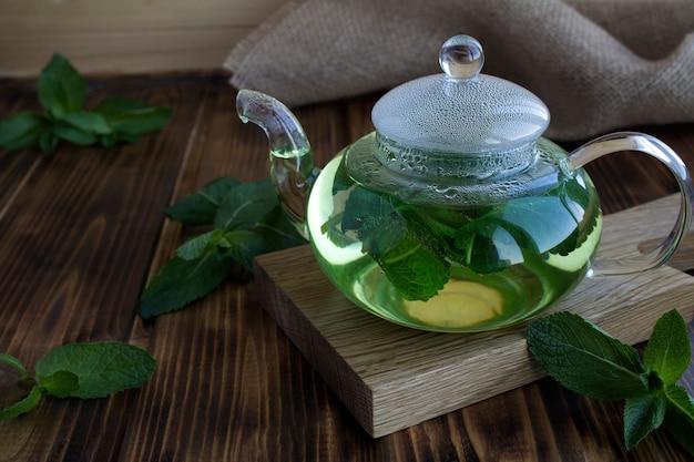 Chá de menta no bule de vidro na mesa de madeira rústica. bebida saudável. fechar-se.