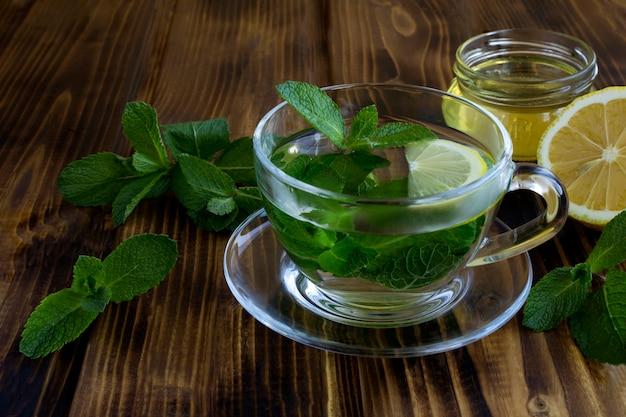 Chá de menta no copo de vidro sobre a mesa de madeira. bebida saudável. fechar-se.