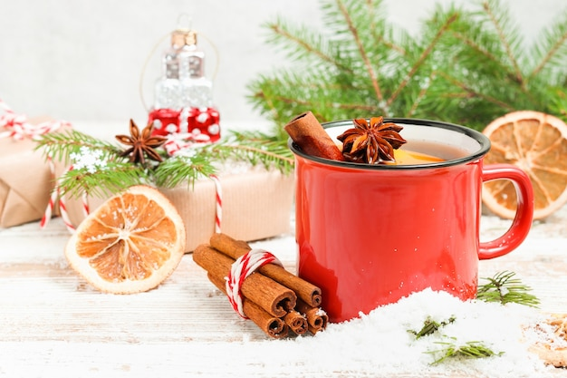 Chá de natal com canela e anis na neve com pinheiro e presentes