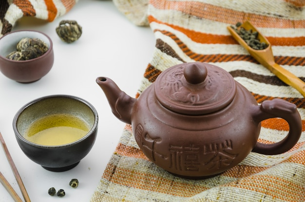 Chá de oolong fresco de cultura de ásia e bule em pano de fundo branco