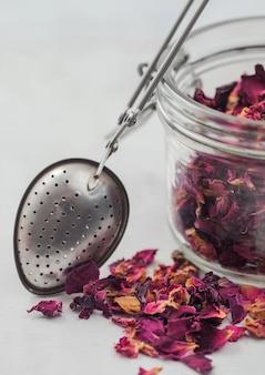 Chá de qualidade artesanal de pétalas de rosa em frasco de vidro com infusor de filtro vintage em fundo branco.
