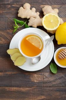 Chá de raiz de gin.ger com limão e mel na mesa de madeira