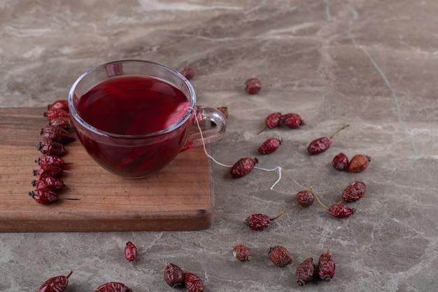 Chá de rosa mosqueta e frutas de rosa mosqueta no tabuleiro, na superfície do mármore