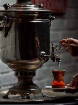 Chá de samovar tradicional colocando em vidro