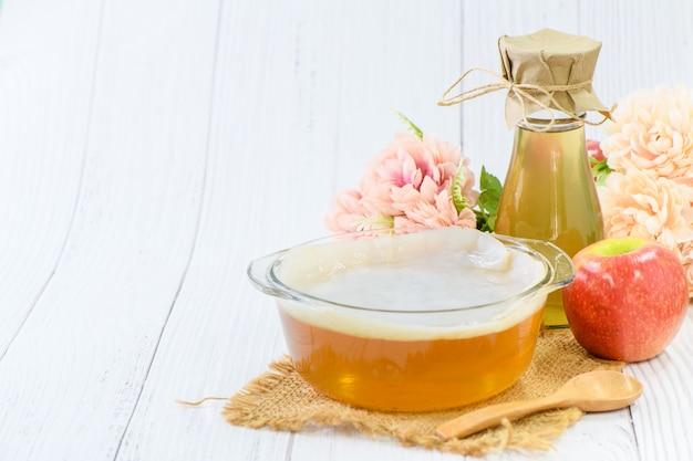 Chá de scoby e kombucha em uma tigela de vidro com fundo de madeira, bebida fermentada de cidra.