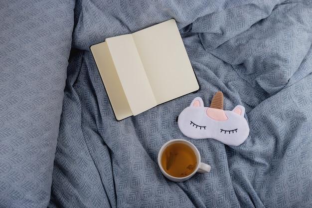 Chá de tília para um sono saudável na cama ao lado de um livro e uma máscara de dormir