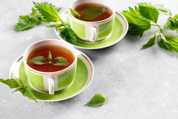 Chá de urtiga em duas xícaras, ervas frescas de urtiga