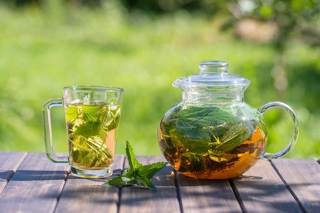 Chá de urtiga saudável em um bule de chá de vidro e caneca no jardim de verão na mesa de madeira. feche o chá de ervas das pétalas verdes de urtiga no fundo da natureza