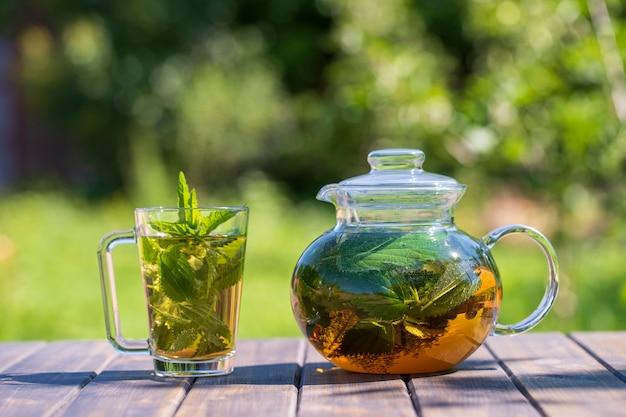 Chá de urtiga saudável em um bule de chá de vidro e uma caneca no jardim de verão na mesa de madeira