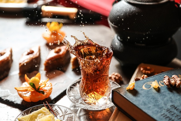 Chá de vista frontal em copo armudu com baklava e um livro sobre a mesa