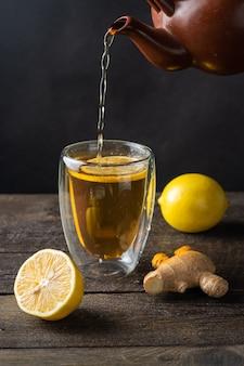 Chá derramado em um copo, um limão, superfície derevyannogm gengibre.