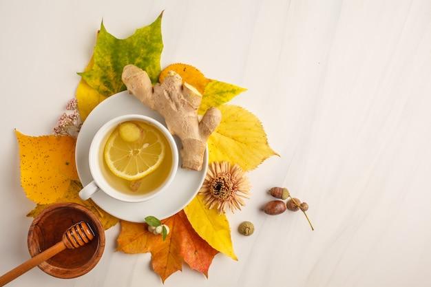 Chá do outono com gengibre e limão em um fundo branco, espaço da cópia.