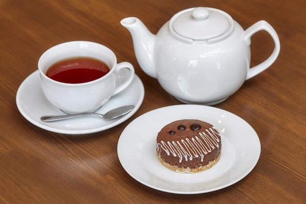 Chá e bolo de chocolate redondo no prato