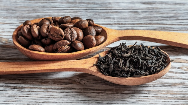 Chá e café em colheres de pau. escolha entre chá e café