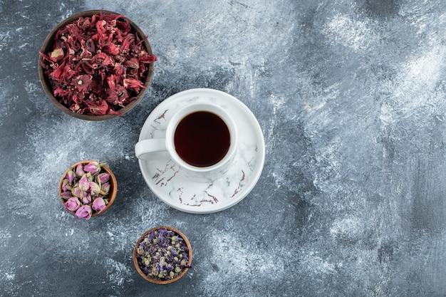 Chá e flores secas na mesa de mármore.