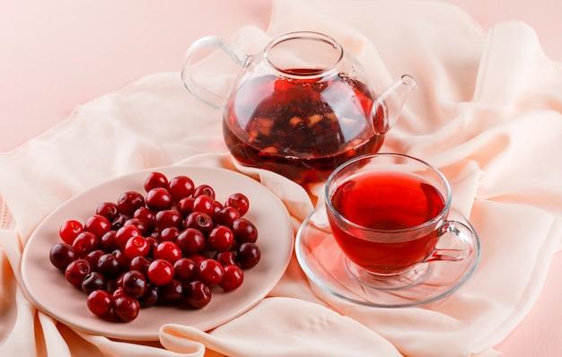 Chá em caneca de vidro e bule com cerejas altas em rosa e têxteis