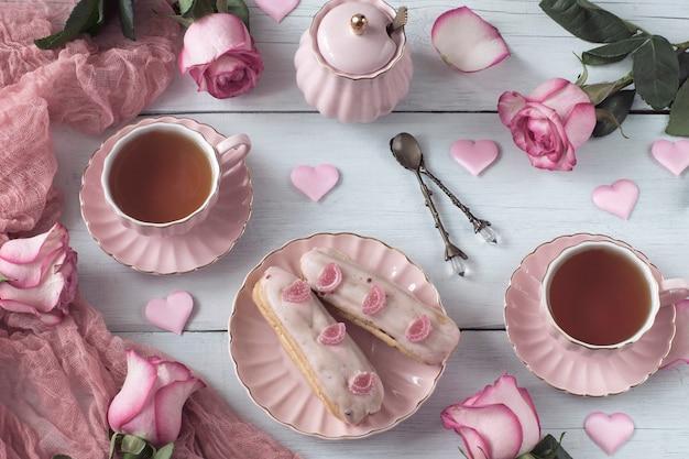 Chá em canecas cor de rosa, corações rosa de cetim, duas rosas eclair e rosas puffins