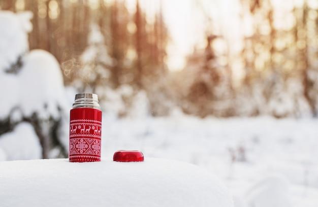 Chá em garrafa térmica vermelha na floresta de inverno