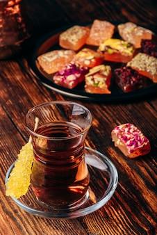 Chá em taça armudu com delícia oriental rahat lokum sobre superfície de madeira