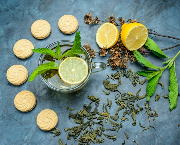 Chá em um copo com limão, biscoitos, hortelã, ervas secas planas leigos sobre uma superfície azul