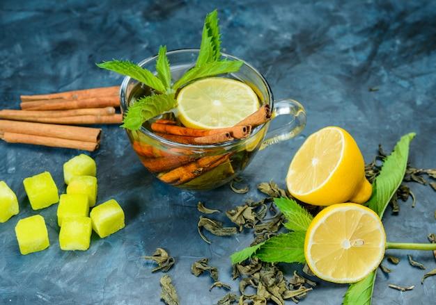 Chá em um copo com limão, hortelã, paus de canela, cubos de açúcar, vista de alto ângulo sobre uma superfície azul