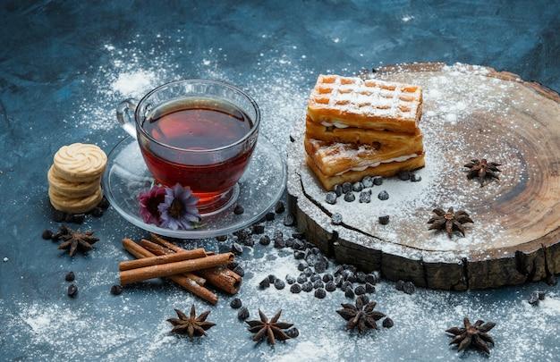 Chá em um copo com waffle, biscoitos, chips de chocolate, especiarias, vista de alto ângulo no grunge azul e placa de madeira