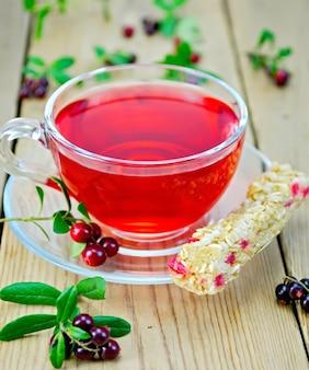 Chá em um copo de vidro com muesli em barra e mirtilos silvestres em um fundo de tábuas de madeira